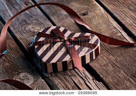 Heart shaped Valentines Day gift box with curved ribbon on old wood. Holiday thematics.