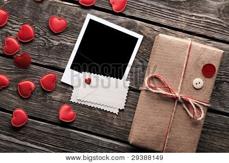 Blank photo frame and vintage gift box (package) with blank gift tag on old wooden background.