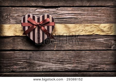 Heart shaped Valentines Day gift box with wrinkled golden ribbon on old wood. Vintage holiday background.