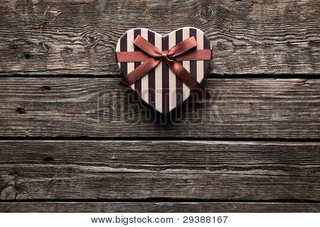 Heart shaped Valentines Day gift box on old wood. Vintage holiday background.