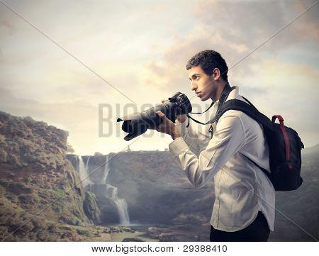 Junge Fotografen halten Sie eine Kamera mit Landschaft im Hintergrund