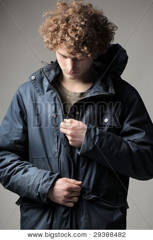 Young man putting on a windcheater