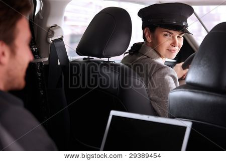 Pretty female chauffeur smiling in luxury car, businessman working on back seat.?