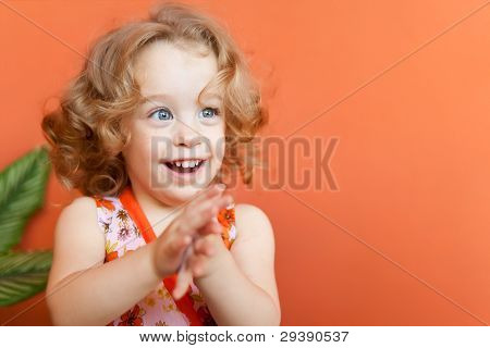 Portrait of a beautiful small girl with gorgeous blue eyes and blonde curly hair clapping her hands on an orange background