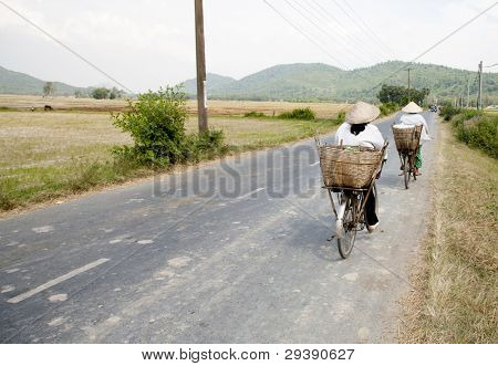 Two cyclists on a rural street in the Mekong Delta, Vietnam