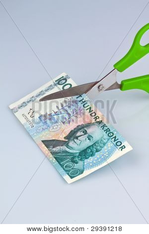 swedish krona, the currency of sweden. with scissors. levies and taxes.