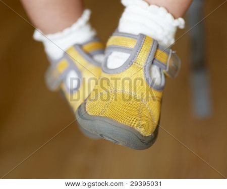 Baby's foot in a pair of yellow shoes.