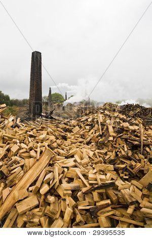 Pila de madera y la chimenea de una fábrica de elaboración de la madera. Se quemará estos leña carbón.
