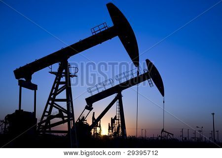 Silhouette of oil pump jacks with sunset
