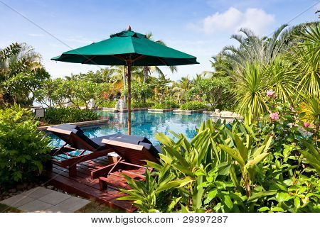 swimming pool with shade and chair in resort garden