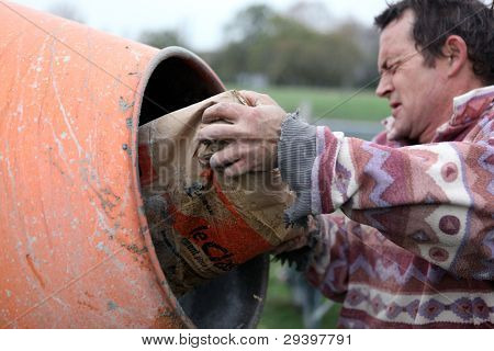 Man putting cement in a mixer