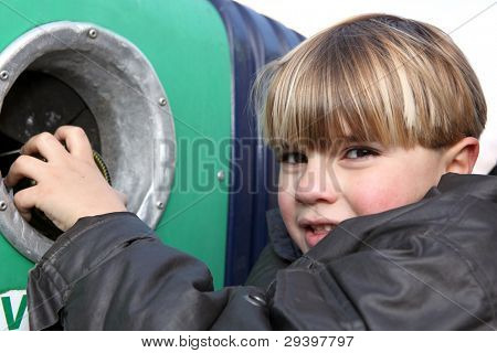 Little boy throwing a glass bottle in a container