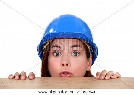 Female builder peering over ledge