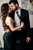 Attractive Woman In Black Dress Holding Tie Of Passionate Man Standing In Suit poster