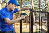 Property Territory Fencing - Man Screws Metal Fence Panel poster