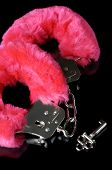 Pink fluffy handcuffs with a key closeup isolated on black background poster