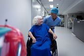 Front view of a Caucasian female surgeon talking with a Caucasian senior female patient sitting in a poster