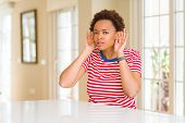 Young beautiful african american woman at home Trying to hear both hands on ear gesture, curious for poster