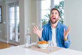 Handsome man eating pasta with meatballs and tomato sauce at home crazy and mad shouting and yelling poster