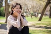 Happy Carefree Asian Girl Relaxing In Park. Young Woman Sitting Outdoors, Leaning Chin On Hands, Sta poster