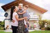 Close-up Of A Happy Soldier Reunited With Family Outside Their Home poster