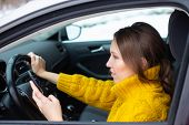 Text And Drive Woman. A Woman Is Texting On Her Phone While Driving poster