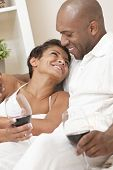 stock photo of black american  - A happy African American man and woman couple in their thirties sitting at home together smiling and drinking glasses of red wine - JPG