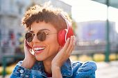 Young smiling african woman listening music with headphones at sunset. Brazilian girl listening song poster