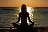 stock photo of breathing exercise  - Silhouette of woman in yoga lotus meditation position front to seaside - JPG