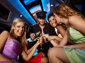 stock photo of champagne color  - Happy girls having fun in limo - JPG