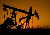 foto of oil drilling rig  - Silhouette of oil rigs with sunset - JPG
