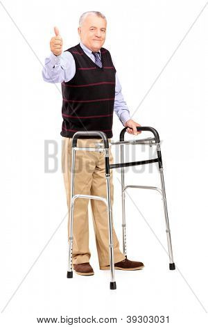 Full length portrait of a mature gentleman using a walker and giving a thumb up isolated on white background