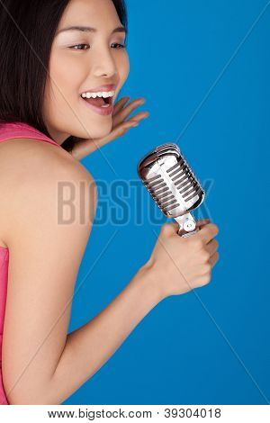 Laughing vivacious Asian woman with a microphone in her hand as she sings and performs on stage on a blue background