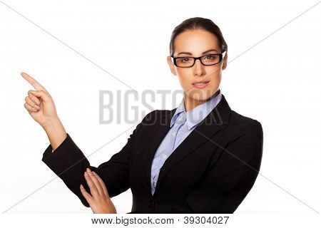 Confident stylish female business executive wearing glasses pointing with her finger to blank copyspace on the left of the frame isolated on white