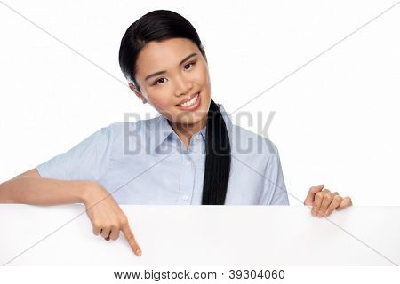 Beautiful young Asian businesswoman pointing to a blank white signboard that she is holding isolated on white