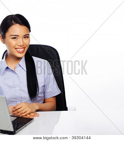 Smiling attractive young Asian businesswoman seated at her desk with a laptop and copyspace