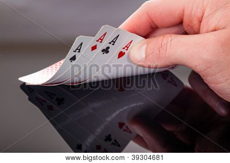 Four aces in the hand on grey background