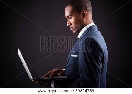 Business black man whit laptop on black background