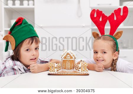 Happy christmas time - children with their gingerbread house, copyspace