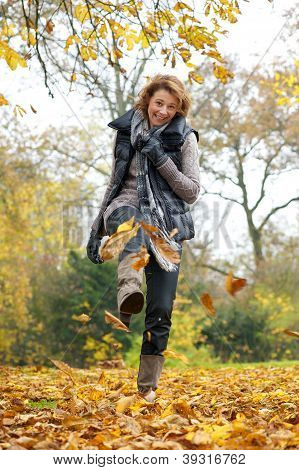 Woman Kicking Yellow Leaves In Autumn