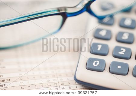 Close-up of glasses lying on calculator on maths tables