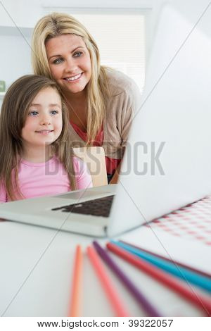 Mother standing behind daughter looking at laptop in kitchen