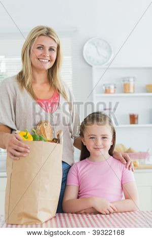 Woman and her little girl smiling at the kitchen with grocery bag on the table
