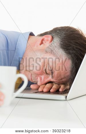 Overworked man holding coffee and sleeping on his laptop on his desk