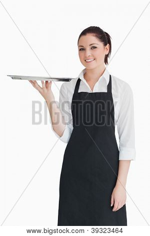 Smiling woman holding an empty silver tray in an apron