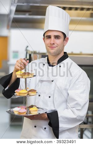 Baker smiling and holding tiered cake tray with cupcakes in kitchen