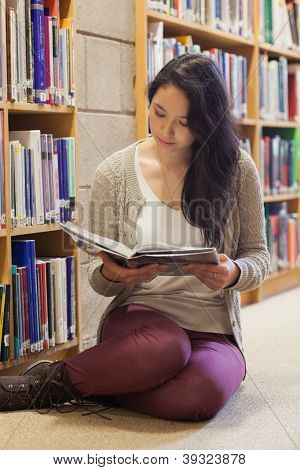 Woman sitting on library floor beside booksshelf reading book