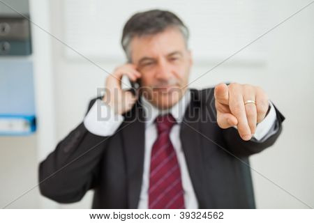 Businessman working with phone while pointing at something in his office
