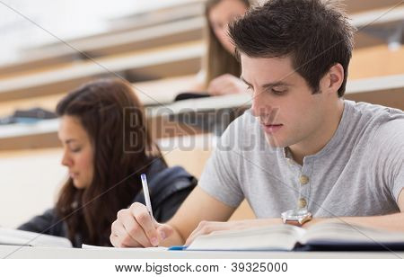 Concentrating students sitting at the lecture hall while writing
