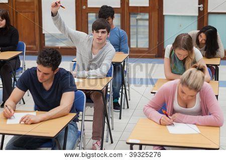 Student raising hand during exam in exam hall in college